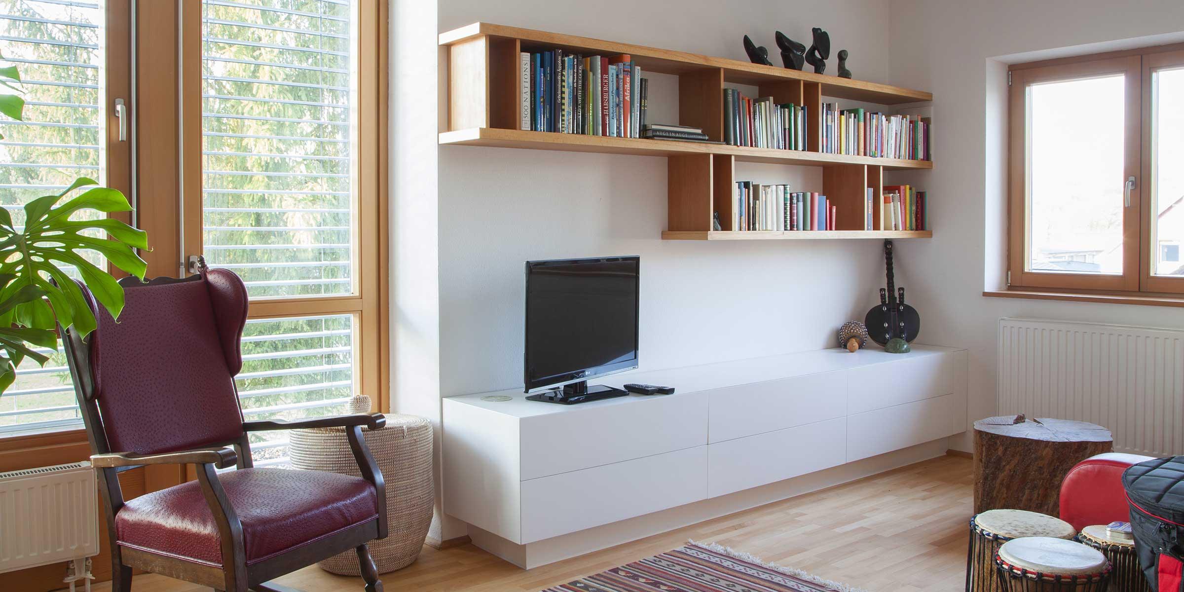 wohnzimmer_verbau_5-Sideboard - deckend weiß, mit 5 grifflosen Lade u. Klappe vor Receiver u. DVD-Player-Bücherboard in Buche geölt Hans Hummer Tischler Innenausbau